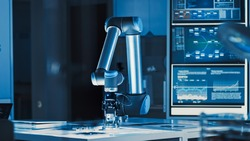 Futuristic Artificial Intelligence Robotic Arm Operates and Moves a Metal Object, Picks It Up and Puts it Down. Scene is Taken in a High Tech Research Laboratory with Modern Equipment.