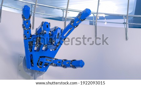 Futuristic big blue mechanical robotic hand with remote control moving fingers and showing devil horn gesture at modern robot exhibition, museum. Science, rock music, future, technology concept Stock photo ©