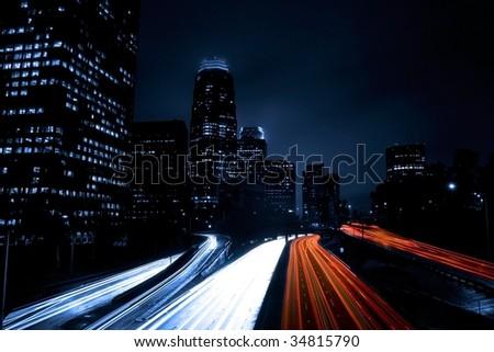 Futuristic City Freeway Traffic into Night Skyline - stock photo