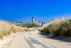 Futuristic city looming at the and of an empty road, which runs through dunes. Summer. Vacation. Vlissingen, the Netherlands. Travel. Path to unknown.Path to success. Journey. Adventure. Destination.