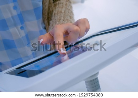 Futuristic, education, entertainment, learning, technology concept. Woman hand using touchscreen display of interactive floor standing white tablet kiosk at exhibition, museum, trade show - close up #1529754080