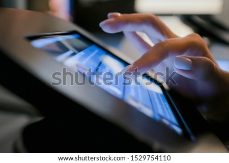 Futuristic, education, entertainment, learning, technology concept. Woman hand using touchscreen display of interactive floor standing black tablet kiosk at exhibition or museum - side close up view #1529754110