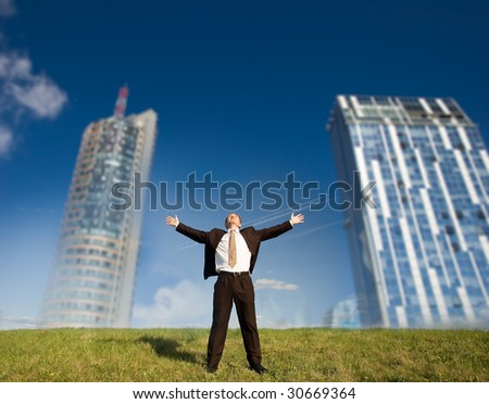 Futuristic freedom - Happy business man standing on green grass - arms outstretched