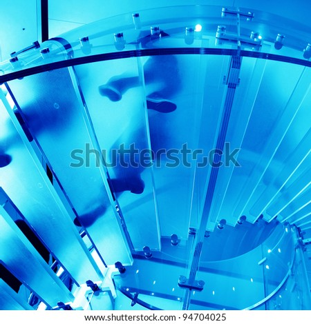 futuristic glass spiral staircase with modern building background