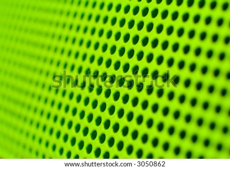 Futuristic green hole grid making an abstract pattern. Shallow DOF.