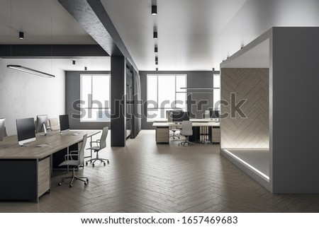 Futuristic grey coworking office interior with equipment and computers on desktop, other pieces of furniture and daylight. 3D Rendering