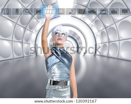futuristic kid girl in silver touching finger icons on glass transparent holographic screen [photo-illustration]