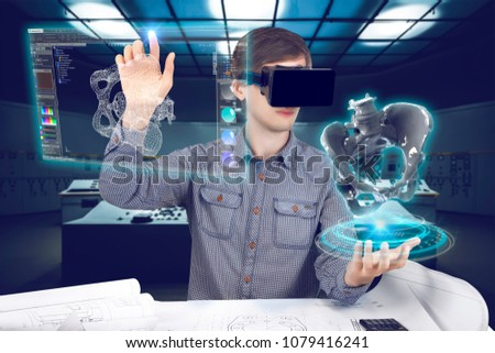 Futuristic medical scientist workplace. Male / man wearing shirt and vr glasses holding holographic prosthesis of coxal and touches virtual screen making medical analysis on futuristic background #1079416241