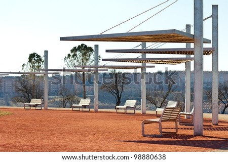 Futuristic park, with benches and canopies for the sun on red sand, with a city behind, selective focus.