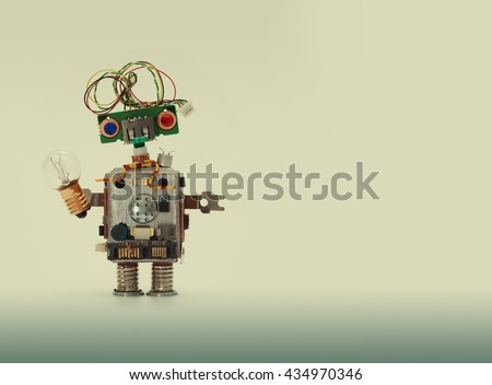 Futuristic robot concept with electrical wire hairstyle. Circuits socket chip toy mechanism, funny head, colored blue red eyes, light bulb in hand. Copy space, beige gradient background