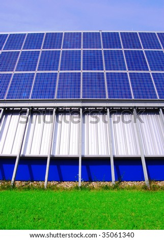 Futuristic solar energy plant on green grass - stock photo