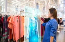 futuristic technology concept.happy girl try to use smart hologram display with virtual augmented reality in the shop or retail to choose select ,buy clothes and change a color of products.