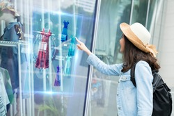 futuristic technology,smart retail online concept.Woman try to use  hologram display with virtual augmented reality in the shop or retail to choose select ,buy cloths and change a color of products