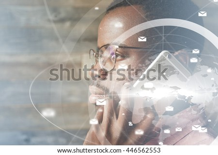 Futuristic technology. Visual effects. Profile of African businessman in glasses, looking into distance with serious expression, holding electronic device at his ear, discussing business on the phone