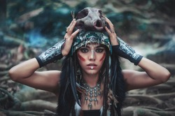 Futuristic tribal indian woman portrait with wolf skull hat outdoors. Blue magical forest on background