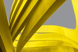 Futuristic urban backdrop. Art arch triangles made of metal in yellow color on grey background. Textured Bright yellow and grey abstract waved background. Trend Color 2021. Copy space