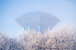 Futuristic water supply tower on cold morning with frost on the trees