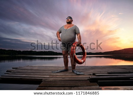 Fuunny overweight, retro swimmer by the lake, at the sunset with copy space