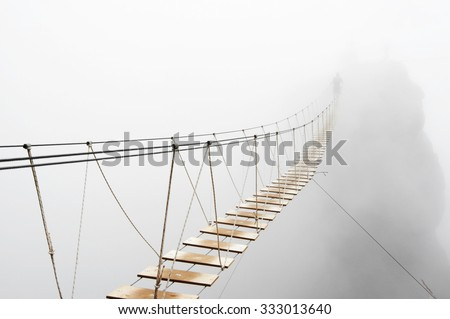 Fuzzy man walking on hanging bridge vanishing in fog. Focus on middle of bridge.  #333013640