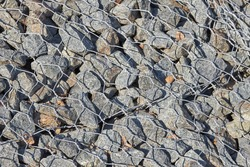 Gabion, a metal basket filled with thick stones. Reinforcement to protect against washouts
