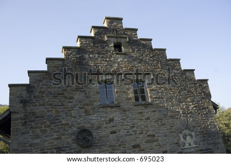 gable of an ancient house built with quarrystones - decorated with a coat of arms