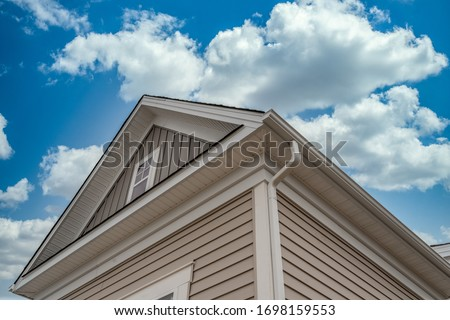 Gable with horizontal vinyl siding, white frame gutter guard system, fascia, drip edge, soffit, on a pitched roof attic at a luxury American single family home neighborhood USA with cloudy blue sky  Stock photo ©