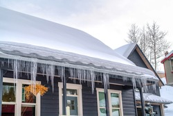 Gabled roof of home covered with thick snow and lined with icicles in winter