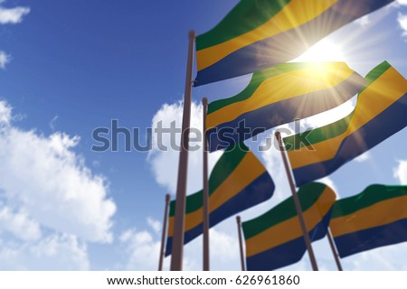 Gabon flags waving in the wind against a blue sky. 3D Rendering
