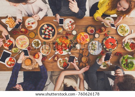 Gadget device addiction, friends dinner with smarphones, online in social networks while eating food together, wooden table top view. #760626178