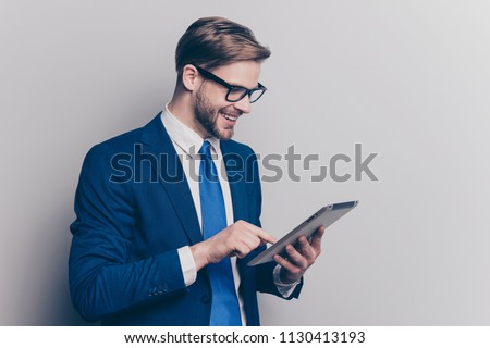 Gadget device innovation app download people person network blogger concept. Side half-turned portrait of excited handsome laughing agent watching videos on tablet isolated on gray background