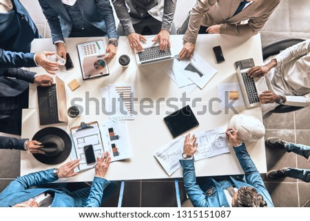 gadgets for business. finance. business people are counting income while sitting at the table . top view photo #1315151087