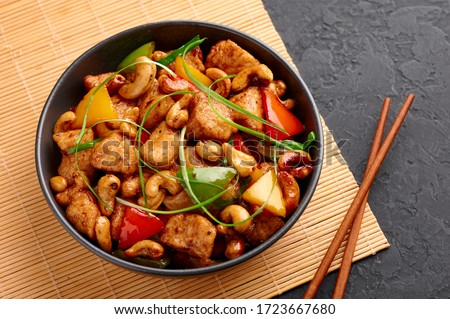 Photo of  Gai Pad Med Mamuang or Thai Cashew Chicken in black bowl on dark slate backdrop. Kai Med Ma Muang is thai cuisine dish with chicken meat, capsicum, onion, scallions, chilli. Thai Food