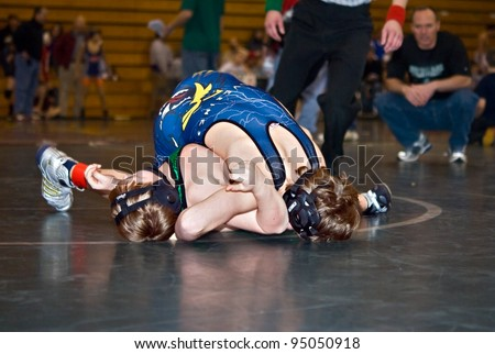 GAINESVILLE, GA, USA - FEB 11: Andy Leggett, the winner, pins an unidentified opponent in the 11-14 division of a wrestling tournament, February, 11, 2012, North Hall High School in Gainesville, GA. - stock photo