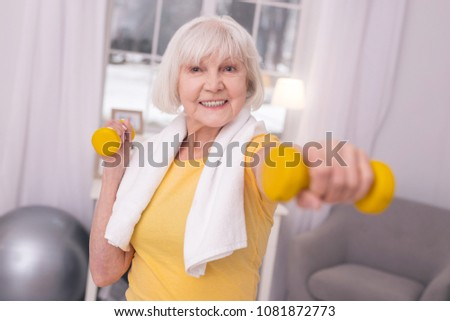 Gaining strength. Upbeat elderly woman with a towel around her neck exercising with a pair of dumbbells and smiling