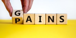 Gains and pains symbol. Businessman turns wooden cubes, changes word pain to gain. Beautiful yellow table, white background. Business, pain and gain concept. Copy space.