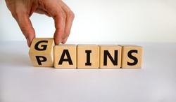 Gains and pains symbol. Businessman turns wooden cubes, changes word pains to gains. Beautiful white background. Business, pains and gains concept. Copy space.