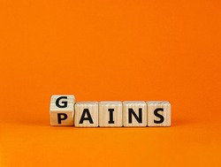 Gains and pains symbol. Turned wooden cubes, changed word pains to gains. Beautiful orange background. Business, pains and gains concept. Copy space.