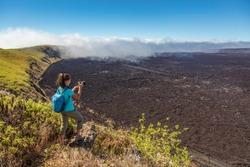 Galapagos tourist hiking on volcano Sierra Negra on Isabela Island taking photos with camera. Woman on hike on famous landmark, worlds 2nd largest active volcanic caldera, Galapagos Islands Ecuador.