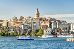 Galata Tower rise above the city, Istanbul, Turkey. It is an attraction of Istanbul. Beautiful panoramic view of the old district of Istanbul in summer. Ships sail on the Golden Horn near Bosphorus.