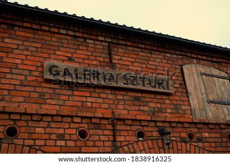 GALERIA SZTUKI means ART GALERY in Polish. The inscription art gallery in Polish on the wall of a red brick building. Zdjęcia stock ©