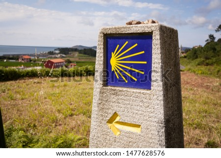 GALICIA, SPAIN - JULY 31, 2019: Camino de Santiago route milestone. Wether you are a pilgrim or not if you follow this yellow on blue shells you can find amazing routes and dream landscapes. #1477628576