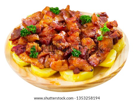 Galician style stewed chopped pork snouts with potatoes served on traditional wooden platter. Isolated over white background