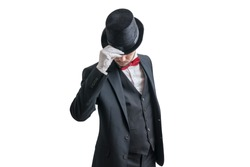 Gallant magician or illusionist in suit is taking off his hat. Isolated on white background.