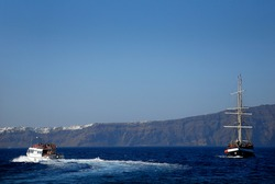 Galleon type tourist boat sailing the Aegean Sea next to a white boat that passes nearby, in the background we see the rock of the city of Thera, Santorini, Greece