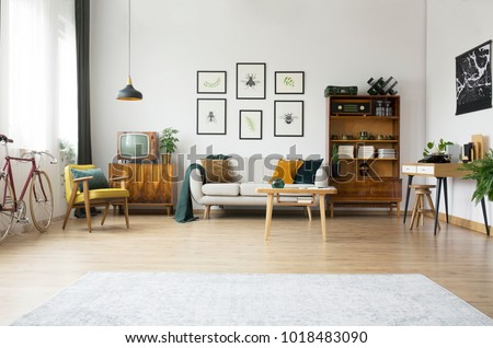 Gallery of posters above settee in spacious living room interior with bicycle, table and vintage furniture