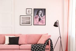 Gallery of posters on empty white wall of bright living room interior with pastel pink settee