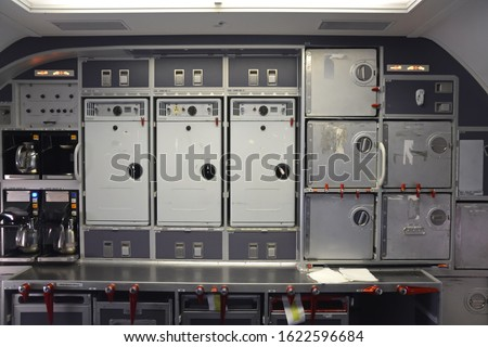 Galley in the back of a commercial aircraft, also know as the kitchen of the airplane. Multiple kitchen accessories in metal like steel and aluminium. Coffee makers visible. Stockfoto ©