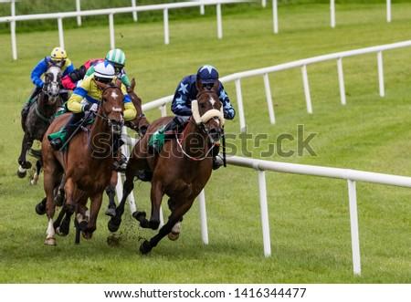 galloping race horses and jockeys  #1416344477