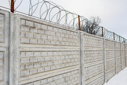 Galvanized, spiral, barbed wire on an openwork fence made of reinforced concrete.  The obstacle creates a reliable barrier that protects from unauthorized persons entering the territory.