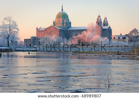 Galway Cathedral in First sunlights and Corrib river covered by ice at cold winter morning